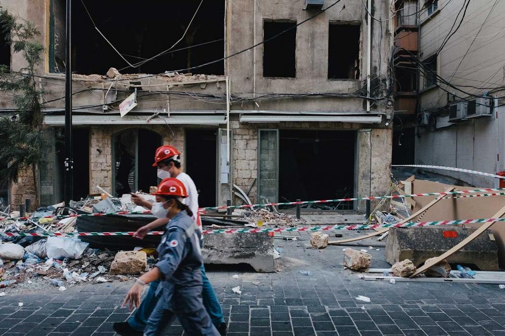 Deux personnes dans la rue devant un immeuble détruit à Beyrouth.